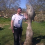 Max with a wooden fish carved from old tree stump